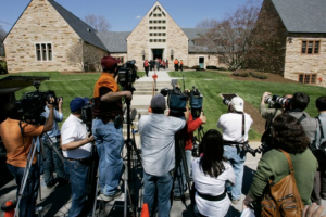 Members of the media photograph attendees of a memorial service after the Virginia Tech shooting. (Photo Credit: AP/Charles Dharapak)